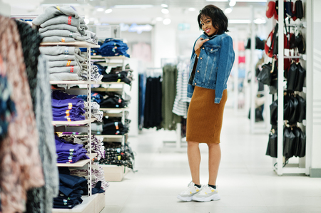 Chic african american woman in brown tunic dress and jeans jacket posed at clothes store. Its time for shopping.