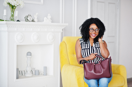 Beautiful african american woman with curly afro hair and eyeglasses, handbag posed in room, sitting on yellow chair.