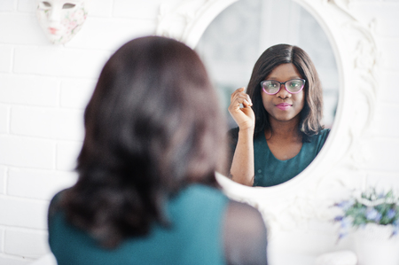 Pretty african american woman in eyeglasses posed in room against mirror.