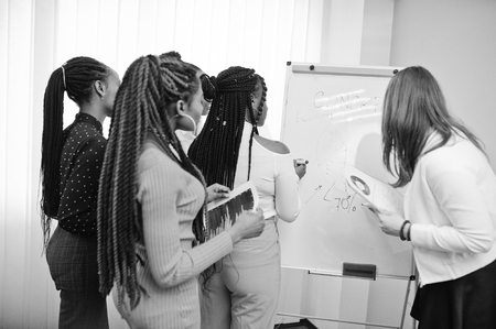 Multiracial women colleagues, crew of divercity female partners in office standing near flipchart.