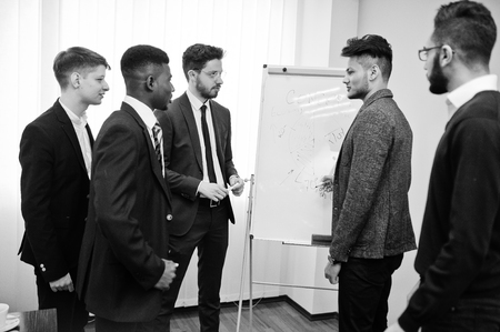 Male colleagues working in team cooperate , multiracial crew of employees concentrated on project planning against flipchart and discussing ideas. Imagens