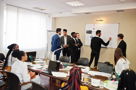 Multiraciaal zakelijk team dat vergadering rond de vergadertafel behandelt en een plan aan boord schrijft.