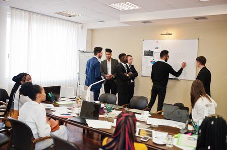 Squadra multirazziale di affari che affronta la riunione intorno al tavolo della sala riunioni e scrive il piano a bordo.