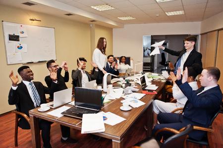 Multirassisches Geschäftsteam, das sich am Sitzungstisch trifft, zwei Teamleiter werfen Papier hoch.