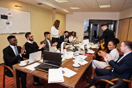 Multiraciale zakelijke teamvergadering rond bestuurstafel, handen klappen. Stockfoto