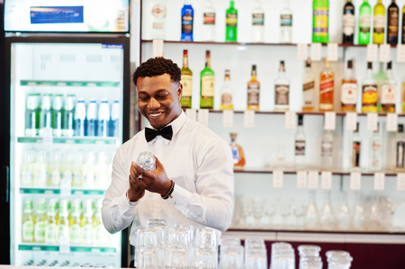African american bartender wear on bow tie cleaning glasses at bar.