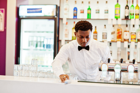 African american bartender wear on bow tie using cleaning glasses at bar.
