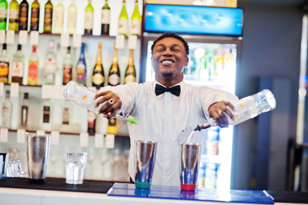 African american bartender working behind the cocktail bar. Alcoholic beverage preparation. Stockfoto