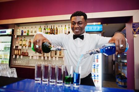 African american bartender at bar making coctails on shots. Alcoholic beverage preparation.