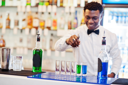 African american bartender at bar making coctails on shots. Alcoholic beverage preparation. Stockfoto