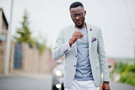 Rich and stylish african american man in blazer and white pants, eyeglasses posed. Imagens