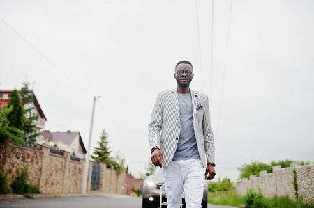 Rich and stylish african american man in blazer and white pants, eyeglasses posed against suv car.