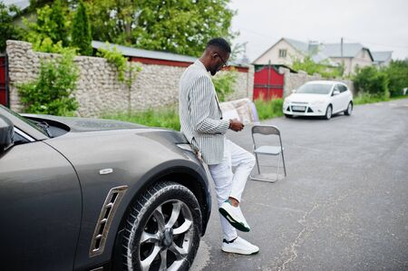 Rich and stylish african american man in blazer and white pants, eyeglasses read magazine against his suv car.