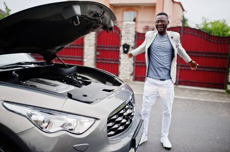 Stylish and rich african american man stand in front of a broken suv car needs assistance looking under opened hood. Reklamní fotografie