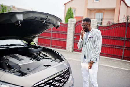 Stylish and rich african american man stand in front of a broken suv car needs assistance looking under opened hood. Imagens