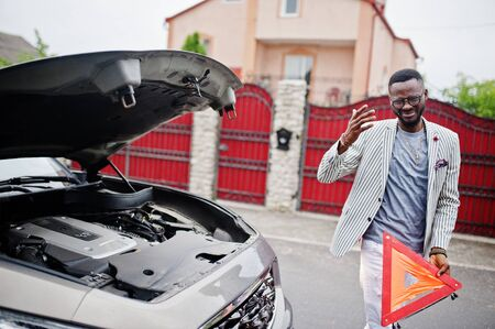 Stylish and rich african american man stand in front of a broken suv car needs assistance looking under opened hood and hold e,ergency triangle. Imagens