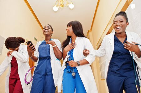 Group of female african medical students in college looking on phone and laughing loud. Stock Photo