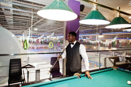 Young handsome african man wearing white shirt, black vest and bow tie play pool billiard.
