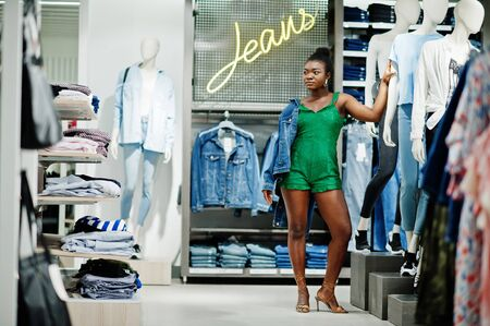Young fashionable and sexy afro woman in green  shopping at clothes store at jeans section.