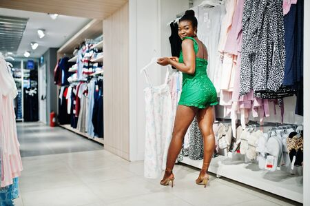 Young fashionable and afro woman in green combidress shopping at clothes store. Nightwear & lingerie sector.