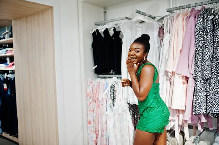Young fashionable and sexy afro woman in green combidress shopping at clothes store. Nightwear & lingerie sector.