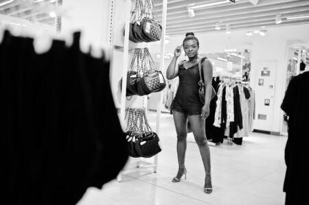 Giovane donna alla moda e afro in verde combidress shopping al negozio di vestiti. Lei sceglie la borsa.