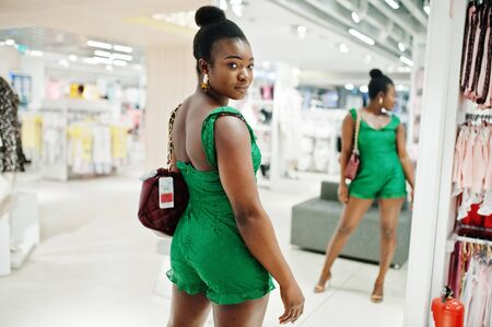 Young fashionable and sexy afro woman in green combidress shopping at clothes store. She choose handbag and looking at mirror.