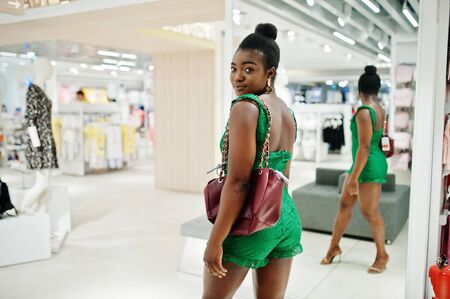 Young fashionable and afro woman in green combidress shopping at clothes store. She choose handbag and looking at mirror.
