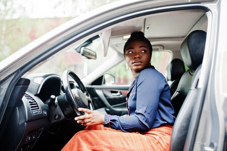 Rich business african woman sit on driver seat at silver suv car with opened door.