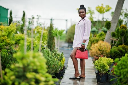 African woman in pink large shirt posed at garden with seedlings.