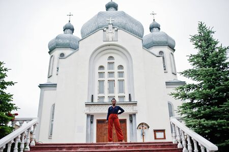 African woman in orange pants and blue shirt posed against large church. Faith and believe on God.