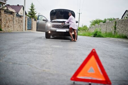 Young sad african woman stand with emergency triangle against car with popped hood. Transportation, vehicles problems and breakdowns concept. Archivio Fotografico