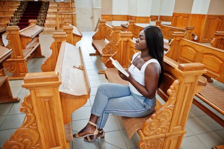 African american woman praying in the church. Believers meditates in the cathedral and spiritual time of prayer. Afro girl hold holy bible while sitting on bench. Imagens