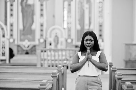 African american woman praying in the church. Believers meditates in the cathedral and spiritual time of prayer. Afro girl folded hands with rosary. Imagens