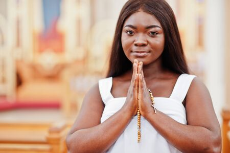 African american woman praying in the church. Believers meditates in the cathedral and spiritual time of prayer. Afro girl folded hands with rosary. Stock fotó