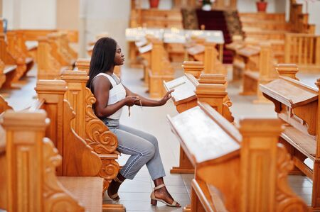 African american woman praying in the church. Believers meditates in the cathedral and spiritual time of prayer. Afro girl hold rosary and sitiing on bench.