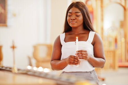African american woman praying in the church. Believers meditates in the cathedral and spiritual time of prayer. Afro girl with candles.