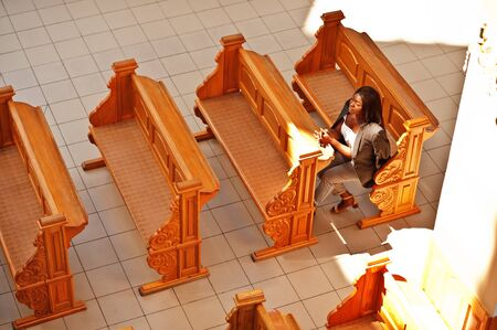 African american woman praying in the church. Believers meditates in the cathedral and spiritual time of prayer. View from above. Stock fotó