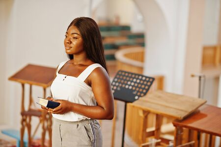 African american woman praying in the church. Believers meditates in the cathedral and spiritual time of prayer. Afro girl with holy bible at hands.