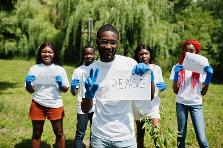 Group of happy african volunteers hold blank board with peace sign in park. Africa volunteering, charity, people and ecology concept.