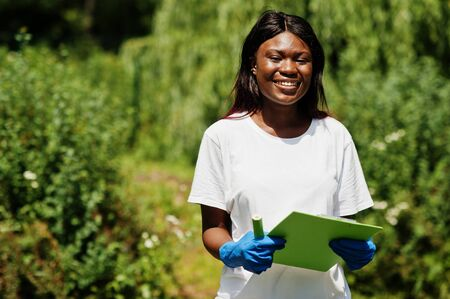African volunteer woman with clipboard in park. Africa volunteering, charity, people and ecology concept.