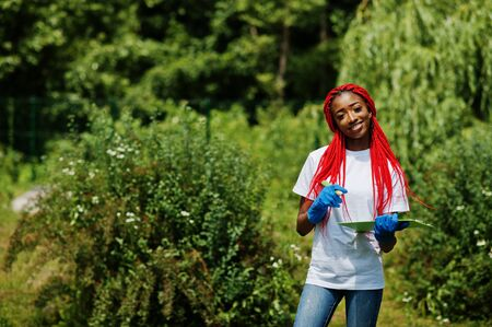 African red haired volunteer woman with clipboard in park. Africa volunteering, charity, people and ecology concept.