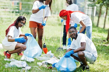 Group of happy african volunteers with garbage bags cleaning area in park. Africa volunteering, charity, people and ecology concept.