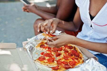Hands of african american woman with pizza.