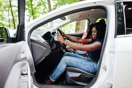 Twee Afrikaanse Amerikaanse meisjesvrienden die pret in de auto hebben. Stockfoto