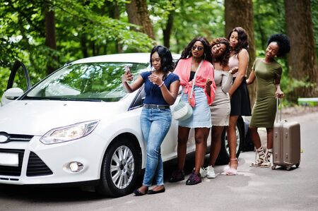 Group of five happy african american traveler girls posed against car with suit bag.