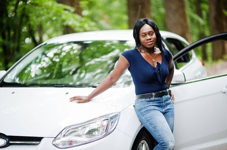 African american woman posed against white car in forest road. Imagens
