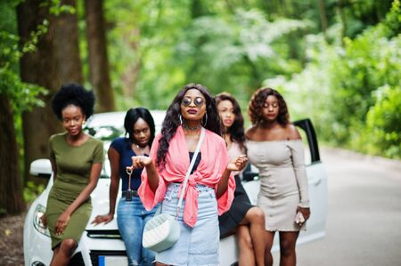 Group of five happy african american girls posed against car, one of them show keys. Imagens