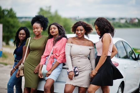 Group of five happy african american girls posed against car. Imagens