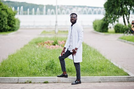 Young african american male doctor in white coat with a stethoscope posed outdoor.